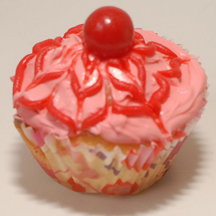 cupcakes with red swirl and candy cherry